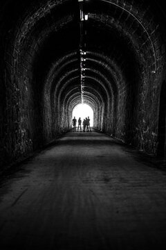 silhouettes of human beings in backlight at the end of a dark tunnel