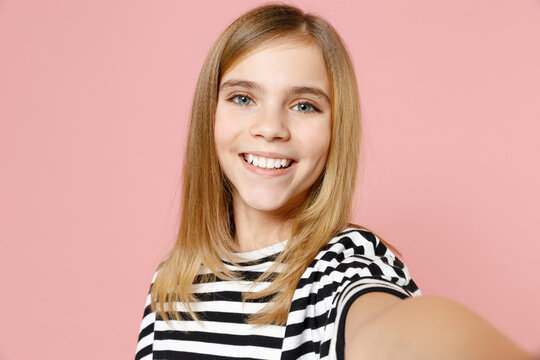 Close up little blonde smiling happy cute kid girl 12-13 years old wearing striped oversized t-shirt doing selfie shot on mobile phone isolated on pink background children Childhood lifestyle concept.