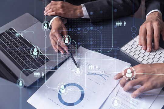 Two HR specialists man and woman analyzing the market of alumni to boost the intern program at international consulting company. Hiring new talented officers. Social media hologram icons.