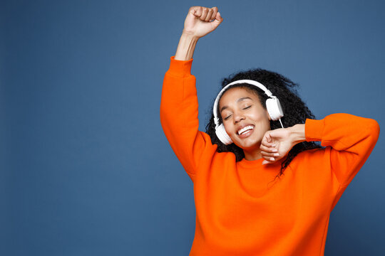 Attractive young african american woman in casual bright orange sweatshirt listening music with headphones dancing rising hands keeping eyes closed isolated on blue color background studio portrait.