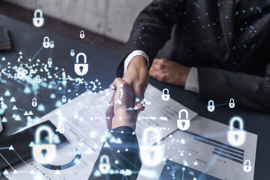 Handshake of two businesswomen who enters into the contract to protect cyber security of international company. Padlock Hologram icons over the table with documents.