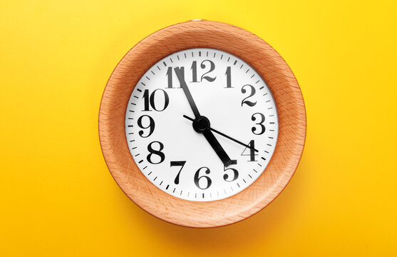 Wooden round clock on yellow background.