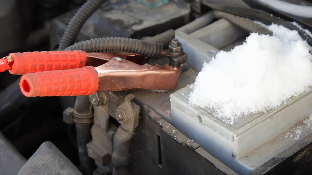 Car engine starting wire red crocodile terminal on frozen snowy car battery + pin close up, Quick start vehicle engine on a winter frost