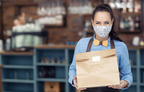Face mask wearing restaurant employee hands over takeaway package during lockdown