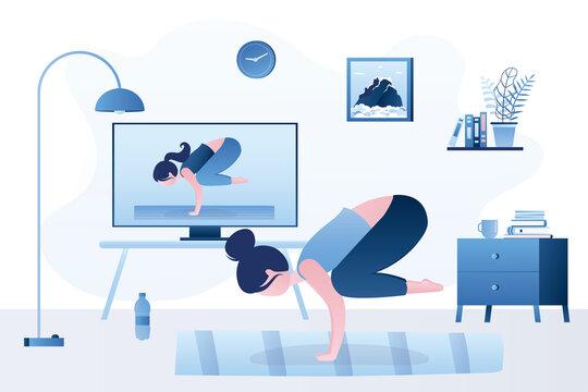 Yoga course streaming on tv or monitor. Girl doing - crane pose, Bakasana asana in hatha yoga. Online technology. Living room interior.