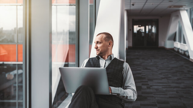 A portrait of a serious relaxed elegant man entrepreneur with a laptop, sprawled on a bench of a modern office hall while looking outside the window on a cityscape; a copy space place on the right