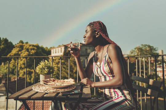 A pensive young dazzling African female in a striped summer jumpsuit is sitting on a balcony of an outdoor restaurant after the rain, drinking wine and eating pizza; a rainbow behind her on the sky