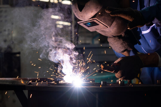 Skillful metal worker working with arc welding machine in factory while wearing safety equipment. Metalwork manufacturing and construction maintenance service by manual skill labor concept.