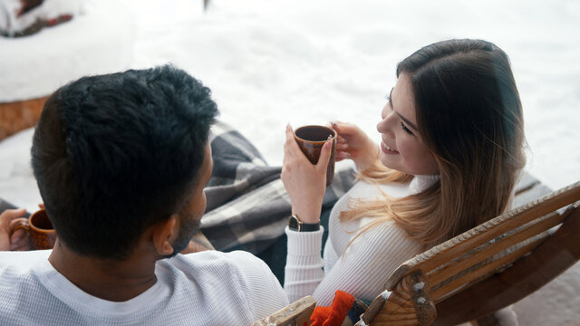 Back view. Happy young couple drinking hot chocolate while sitting on the bench outdoors on Valentines day. High quality photo