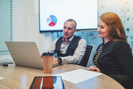 A business scene in a conference room with two colleagues: a woman entrepreneur is looking at the screen of the laptop of her male colleague a businessman where they see other members of the videocall
