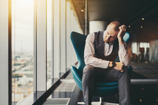 A tired depressed businessman in a luxury office settings sadly looking outside the window; a man entrepreneur on an armchair is worrying about his dismissal and the bankruptcy of the company