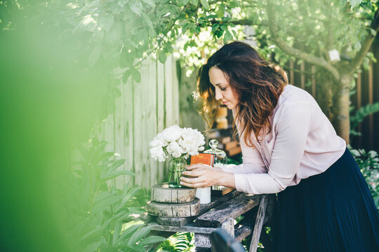 Pretty woman wearing pink blouse puts glass vase with beautiful white peonies near candles and gifts on wooden table near fence in summerhouse yard.