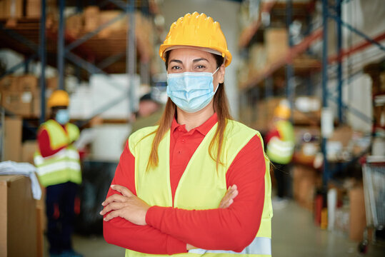 Portrait of happy female worker looking at camera inside warehouse while wearing face mask - Focus on face