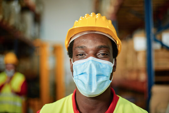 Portrait of an African worker inside a warehouse with safety mask - Focus on the man's eyes