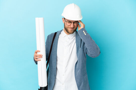 Young architect man with helmet and holding blueprints over isolated background with headache