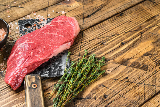 RawStriploin steak on a meat cleaver, marbled beef. Wooden background. Top view. Copy space