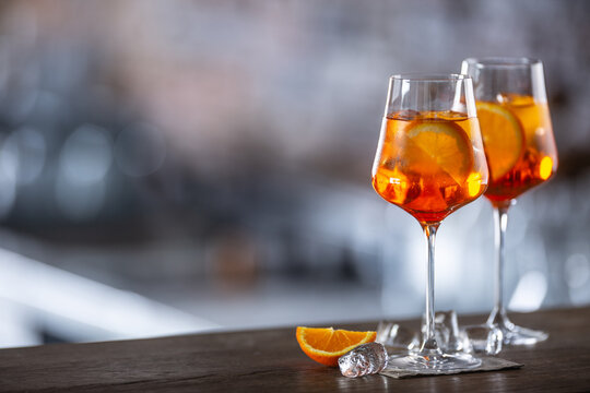 Typical summer sekt drink aperol spritz served in wine glass with aperol, prosecco, soda and a slice of orange