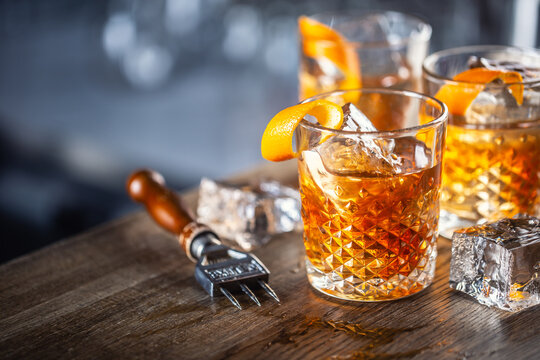 Old fashioned classic rum cocktail on ice with orange zest garnish
