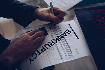 Close-up of a man's hand signing a bankruptcy document. Business bankruptcy.