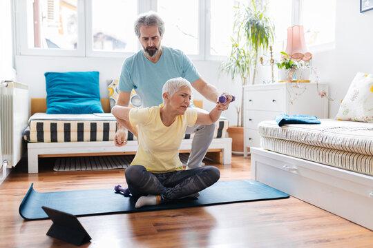 Senior couple doing exercises at home. Senior man helping senior woman doing exercise. Lower back pain