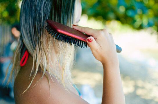 Close-up Of Woman Brushing Hair At Beach