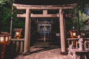 Girl and rabbit statue, stone torii gate and little shinto altar with bell and wooden lamps at Yasaka shrine in night, Kyoto, Japan