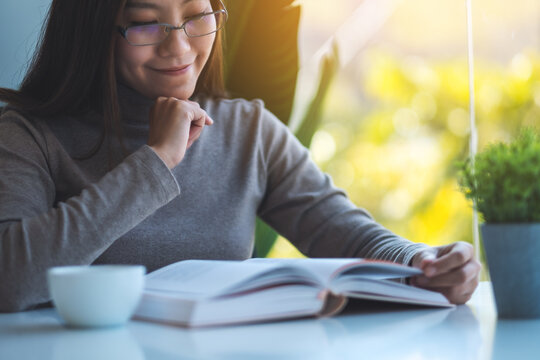 Closeup image of a beautiful young asian woman with eye glasses reading book at home