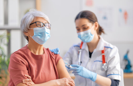 Doctor vaccinating a senior woman