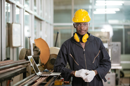 Portrait of black male african american workers wear sound proof headphones and yellow helmet standing an iron cutting machine in factory Industrial.