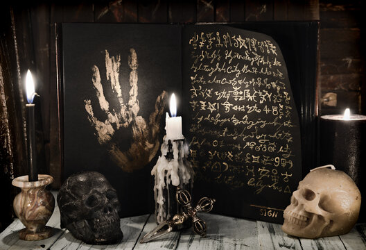 Sell soul to the devil concept with open book with black pages and golden mystic symbols.