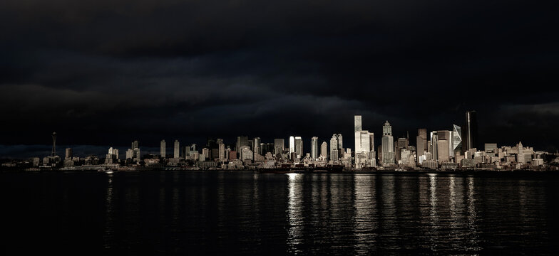 Panaramic view of Seattle citycape with dramatic light as seen from Alki Beach in West Seattle over the water of the Puget Sound