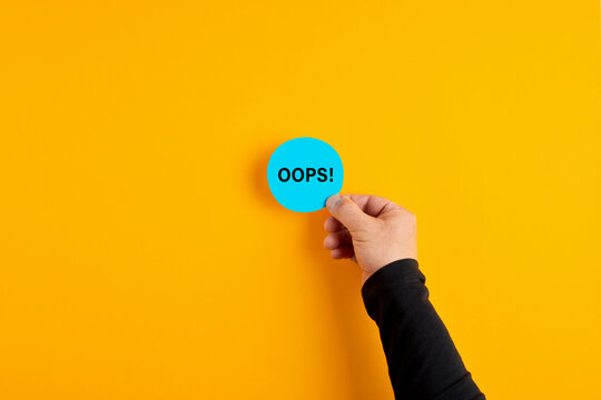 Male hand placing a blue badge with the word oops on yellow background.