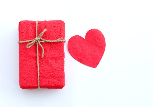 red gift box and red paper heart on white background