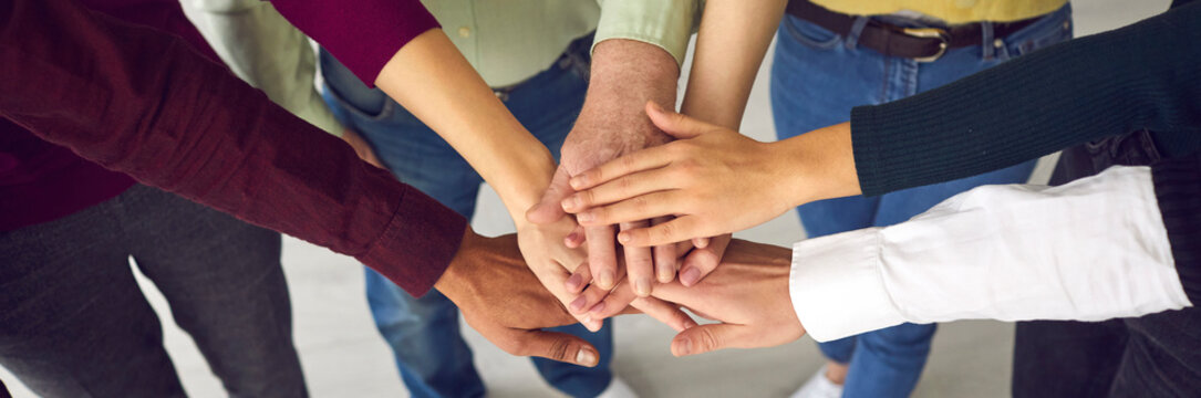 Top view of a group of people of different ages and nationalities fold their arms as a symbol of cooperation. Concept of teamwork, cooperation, unity, trust and support. Close up.