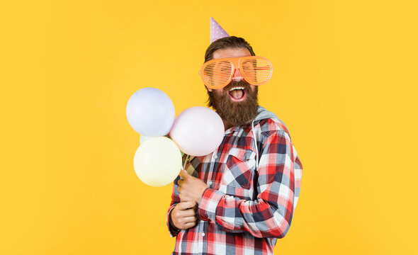 Buying gifts. happy man with beard. man in party glasses hold balloons. holiday celebration. happy birthday to you. corporate party celebrate. hello summer. summer vacation party. feel the happiness
