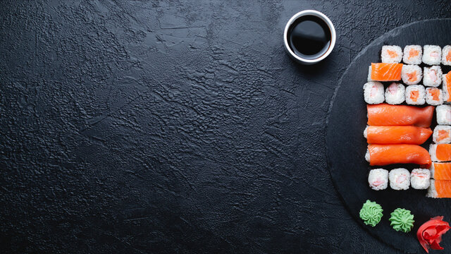 Sushi rolls with salmon, rice, eel and soy sauce on dark stone background, space for text, large banner