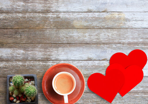 Top view red paper heart and coffee on wood table background with copy space for you desing.