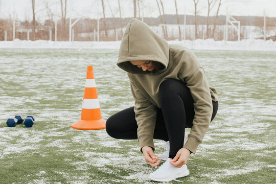 Woman prepares for training outside in winter. lady tying her shoelaces in the stadium on green sports floor