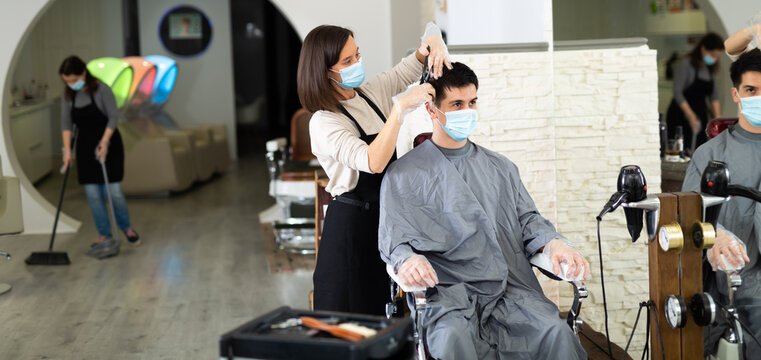 Female hairdresser making hair styling for young man in protective mask and gloves, working day during pandemic situation