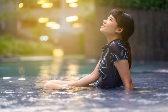 Side View Of Woman Sitting In Swimming Pool