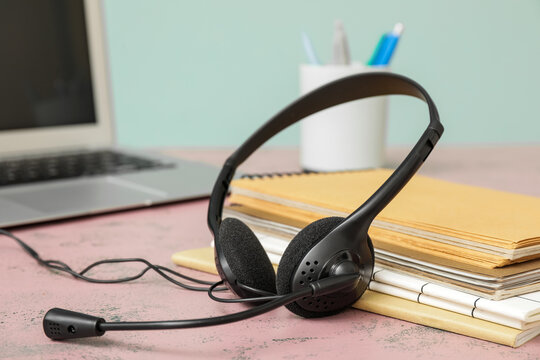 Headset with notebooks on table in office