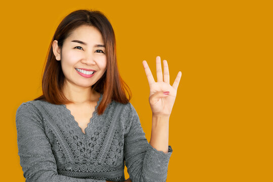 happy Asian making hand gesture showing her fingers age 40s year old with confident face