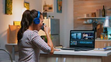 Woman video editor with headset working with footage and sound sitting in home kitchen. Woman videographer editing audio film montage on professional laptop sitting on desk in midnight