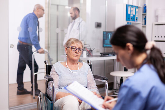 Senior retired patient seeking medical advice and treatment in modern clinic. Medical specialist wearing stethoscope discussing with invalid elderly woman in consultation room of private.
