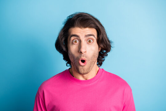 Photo of young startled wavy hair man wear casual cloth standing open mouth isolated on blue color background