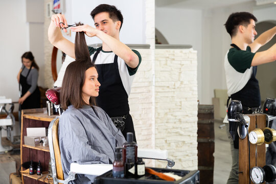 Young man professional hairdresser cut female's hair in hairdressing salon