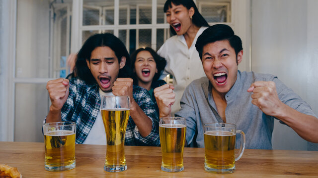 Group of tourist young Asia friend watching football in sports TV, drink alcohol beer and having hangout party in night club at Khao San Road. Traveler backpacker people travel in Bangkok, Thailand.