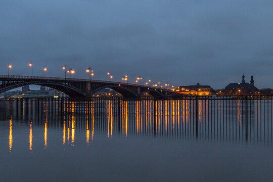 Beleuchtete Brücke über den Rhein bei Mainz an einem Winterabend mit Hochwasser