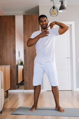 African-American man doing shoulder rotation exercise during working out at bright domestic room. Concept of sport training at home gym.