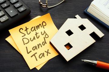 Fototapeta Stamp duty land tax SDLT memo and model of home.